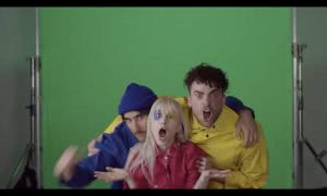 paramore posing infront of green screen behind the scenes of the hard times music video wearing blue, red and yellow