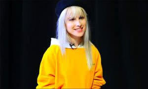 Hayley Williams wearing yellow on black background blonde