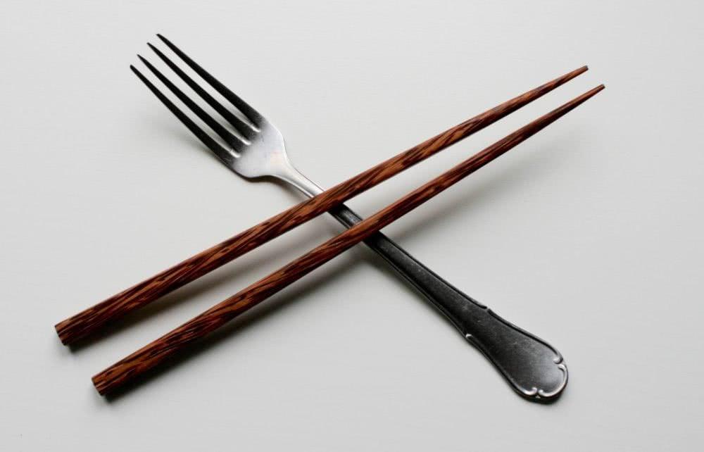A pair of chopsticks crossing a fork.