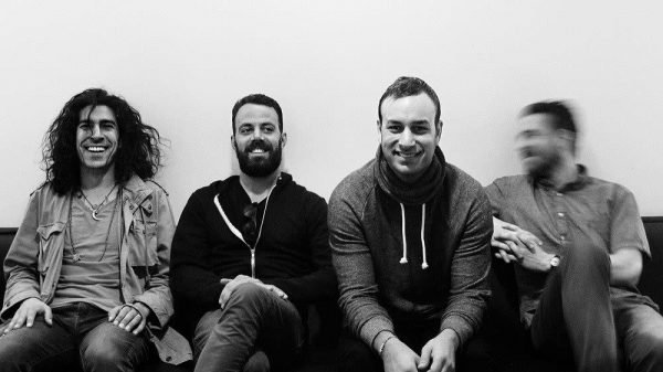 The members of Brand New in front of a white wall