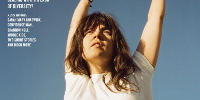 Courtney Barnett, wearing a white t-shirt, swings on gym rings in front of palm trees
