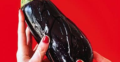 An eggplant being held by hands with red nailpolish whilst lube is dripped on it