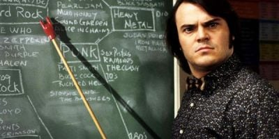 Jack Black looking at the camera in a black and white shirt standing in front of a black board