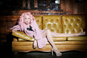 Cyndi Lauper with pink hair wearing a pink dress sitting on an orange lounge