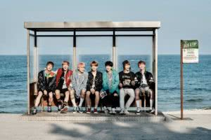 seven men sitting at a bus stop in front of the ocean