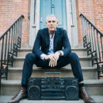 Lyor Cohen press shot 2016 sitting on steps