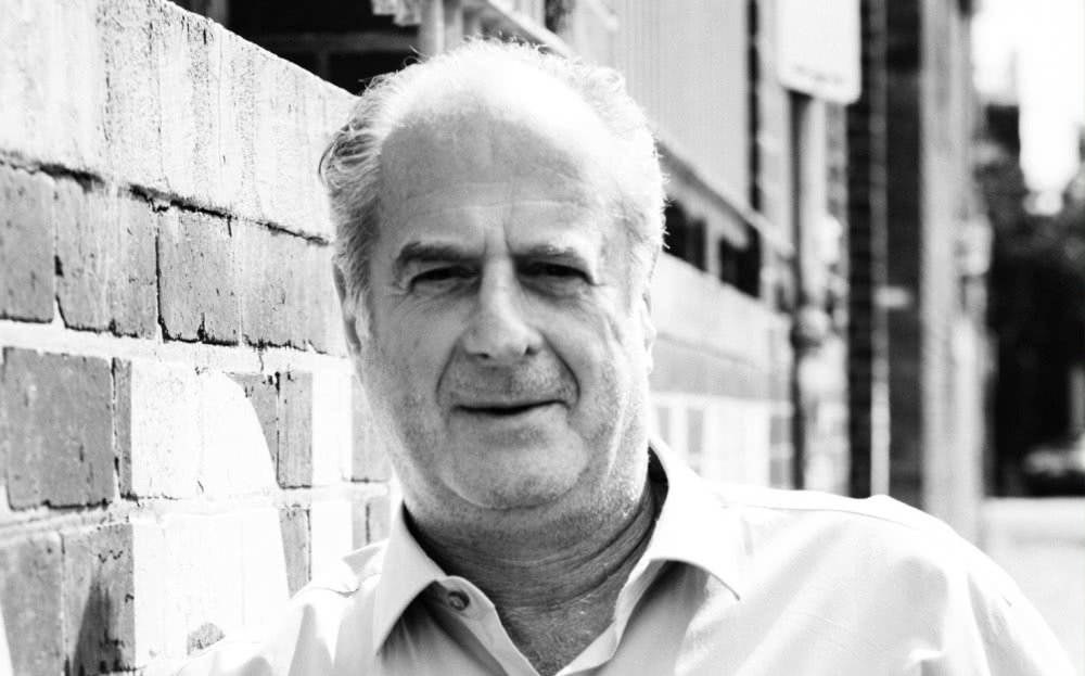 Black & white close up image of Michael Gudinski leaning against a brick wall for good neighbour of power players